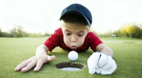 Young Boy Cheating at Golf